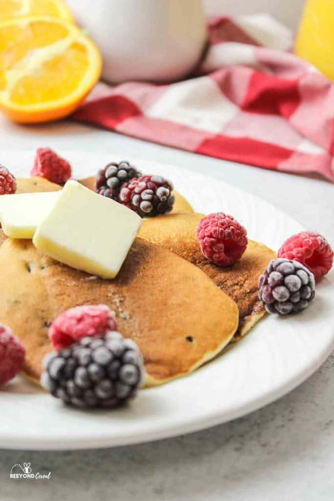 a plate of stacked pancakes next to a package of blueberry muffin mxi