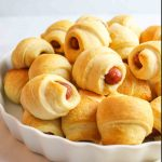 a side view of half a serving dish filled with golden colored pigs in a blanket