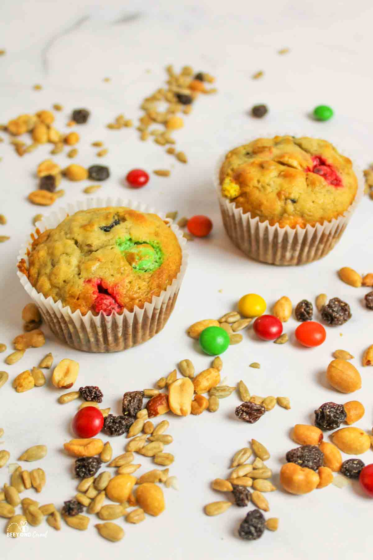 two trail mix banana muffins with trail mix around them