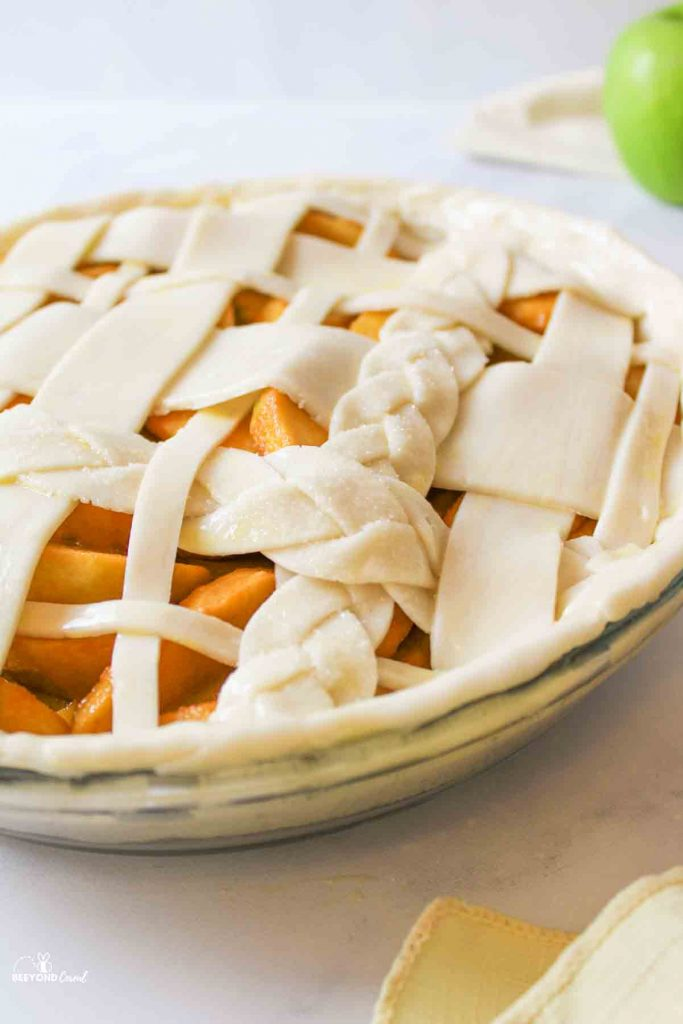 an unbaked butterscotch aple pie with a braided lattice top and a green apple in the background