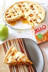 a sliced apple pie with a bow of pudding mix and green apples to the side