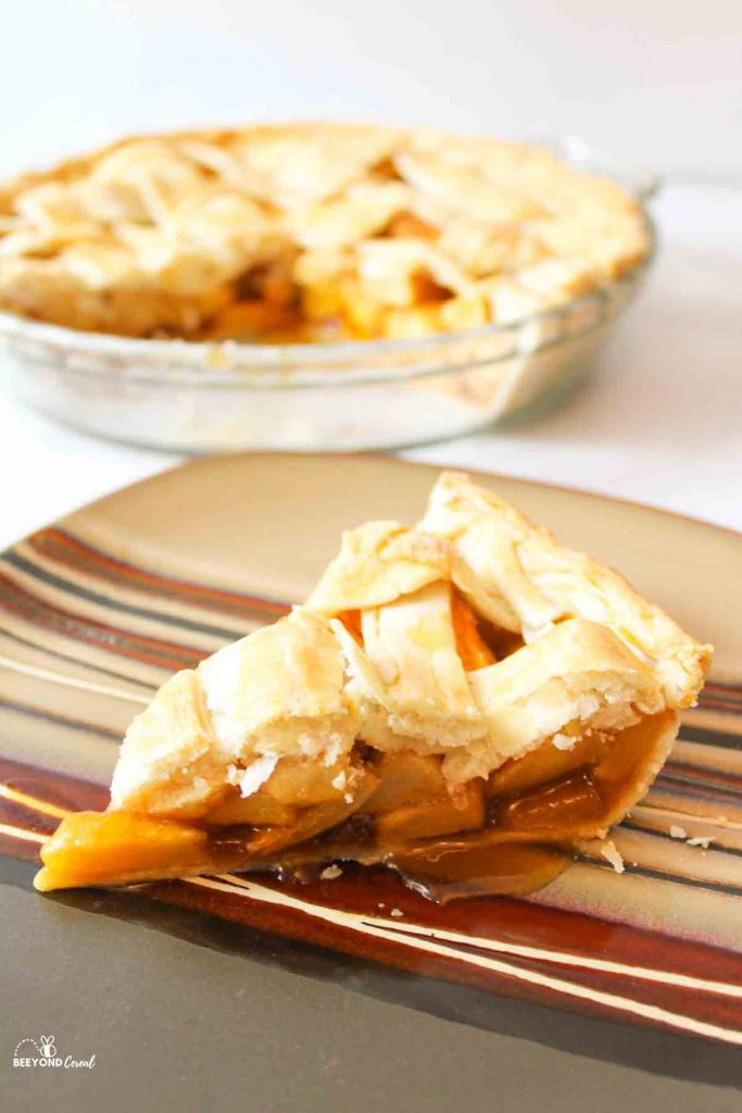 a sideways slice of butterscotch apple pie with the remaining pie in the background