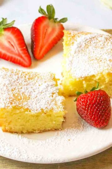 side view of a sliced lemon bar square and fresh strawberries around it