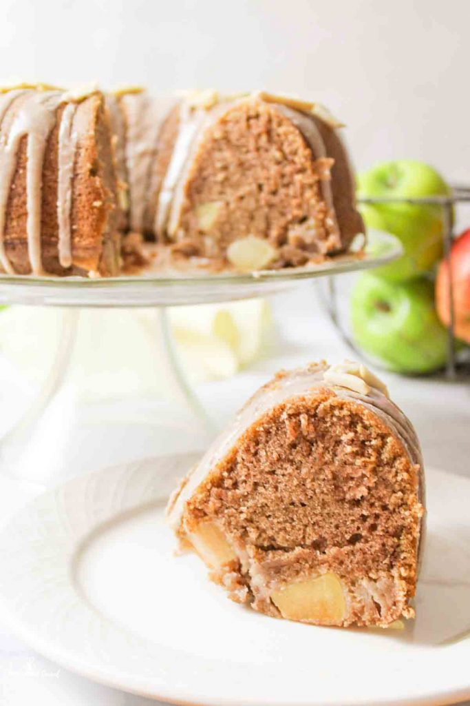 a sliced apple bundt cake with one slice on a plate below a cake stand with the remaining cake on it and fresh apples in background