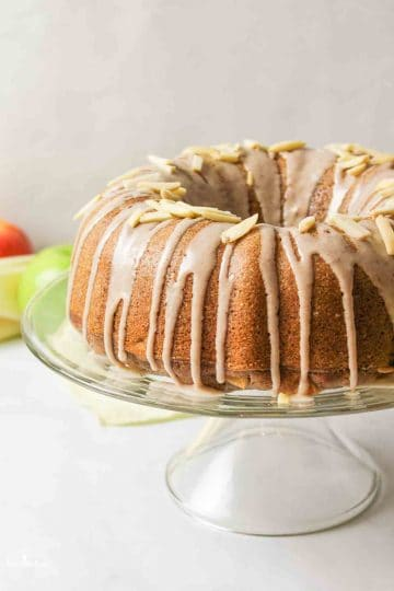 a close side view of a glazed apple bundt cake on a cakestand