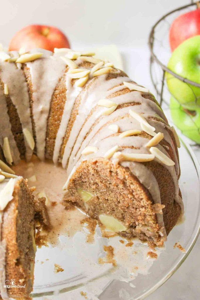 a sliced apple bundt cake with glaze and fresh apples in the background