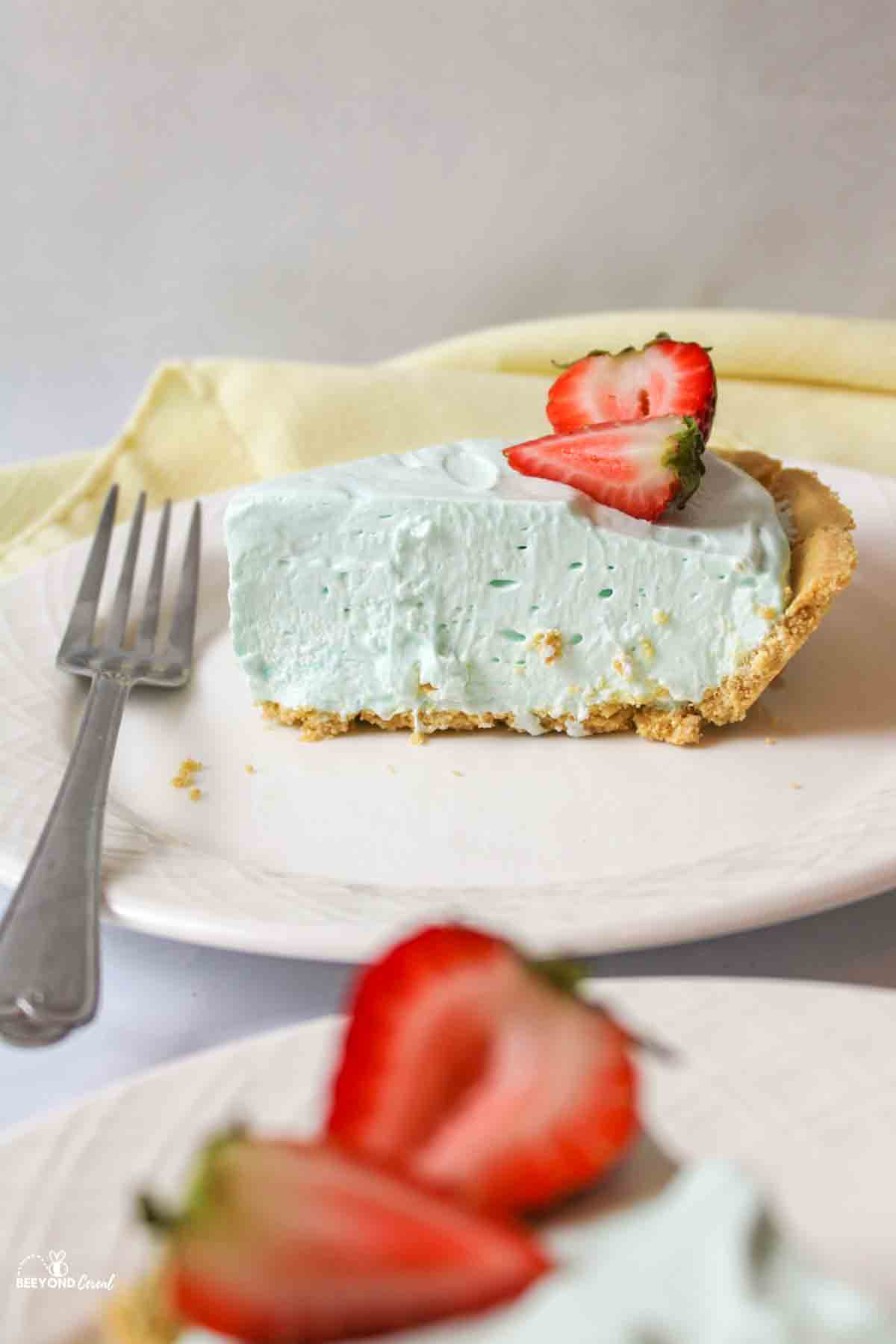 a slice of blue kool aid pie topped withhalved strawberries and a fork to the side