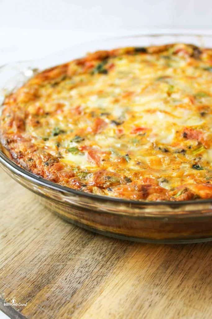 a sie view of a glass pie plate filled with baked veggie quiche