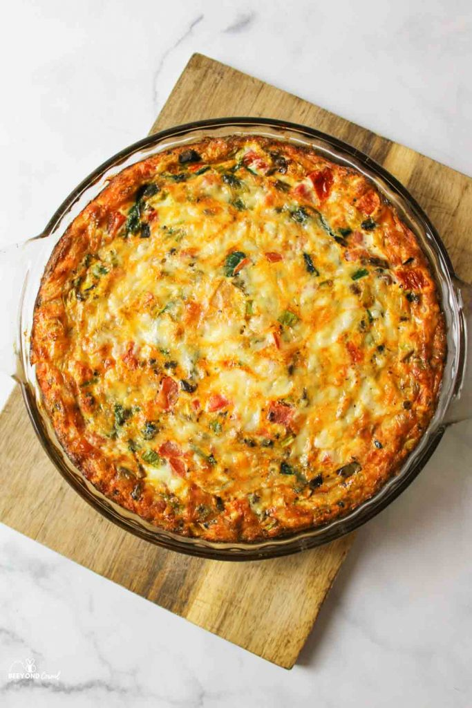 aerial view of baked veggie quiche in a glass pie plate on a wooden cutting board