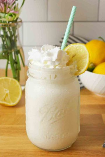 an upclose view of a mason jar filled with frozen whipped lemonade and fresh lemons in the backgorund