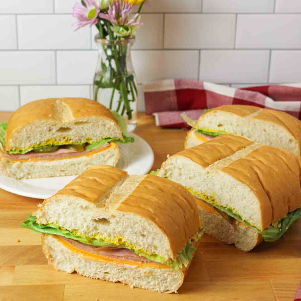 an upclose view of 4 slices of a giant sub sandwich with one in the background on a white plate