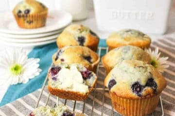 a close up of blueberry muffins on a cooling rack with one split in half and topped with some butter