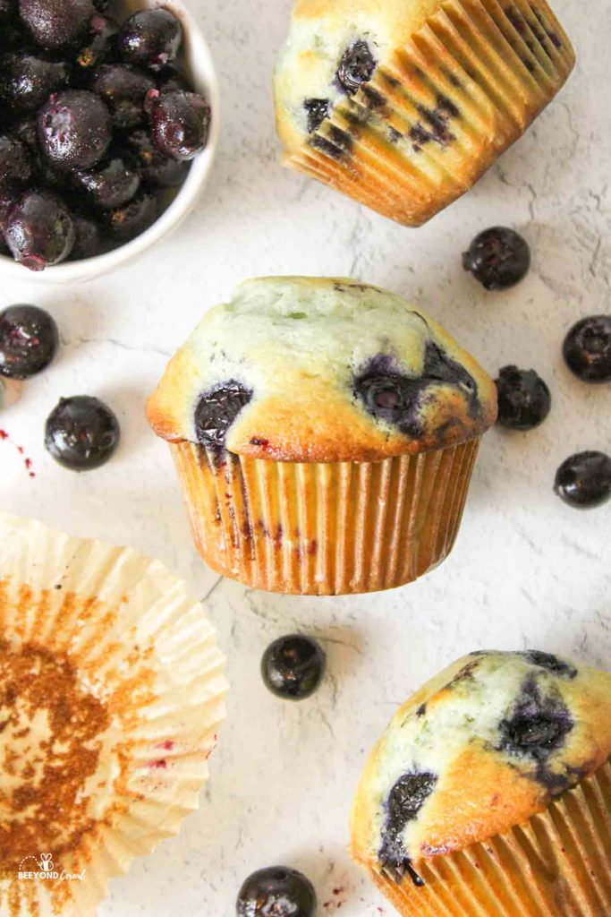 an upclose view of a blueberry muffin on its side surrounded by blueberryies and more muffins
