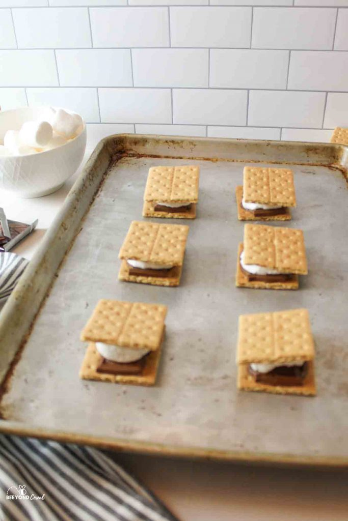 6 broiled smores on a bking sheet with a bowl of marshmallows in the background to the left