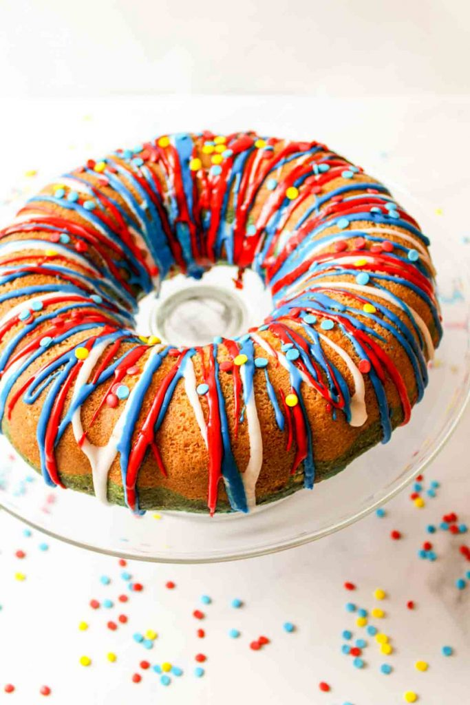 a red white and blue patriotic bundt cake on a glass cake stand with sprinkles scattered around