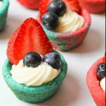 an upclose view of several red and blue cookie cups with frosting and berries inside