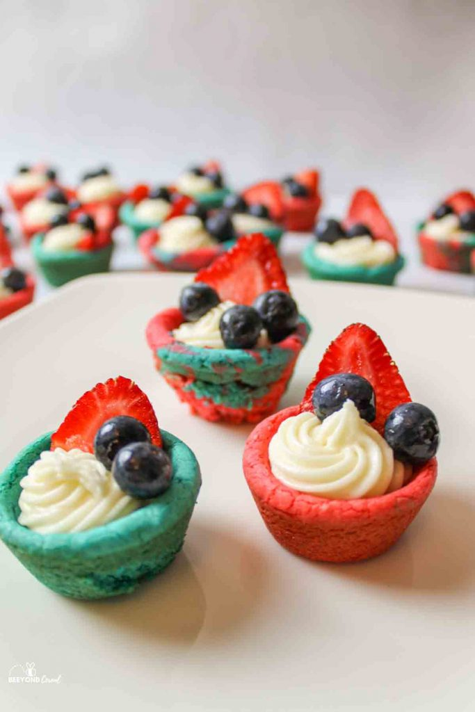 three red and blue cookie cups with frosting and berries inside