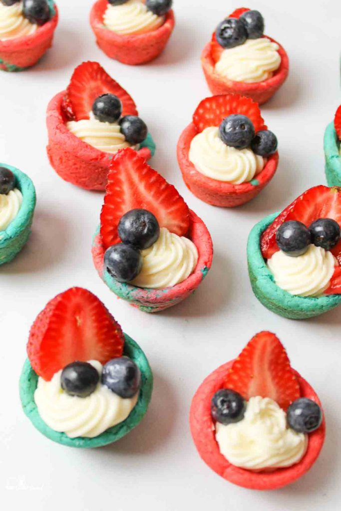 scattered and arranged red and blue cookie cups filled with cream cheese frosting and fresh strawberry slices and blueberries