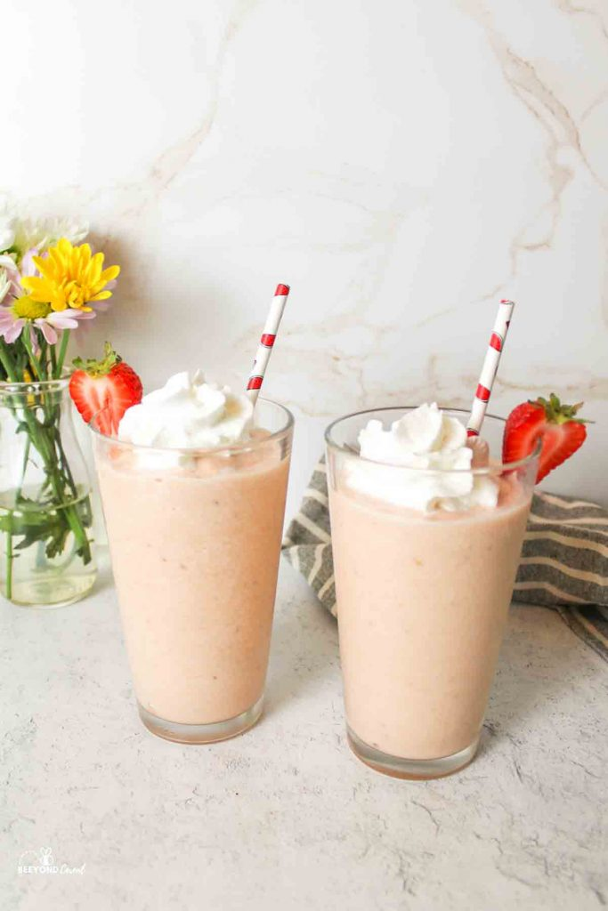 two drinking glasses full of watermleon smoothie and topped with whipped cream, straws, and strawberry slices