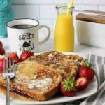 an upclose view of french toast on a plate with fresh strawberries and coffe and orange juice in background