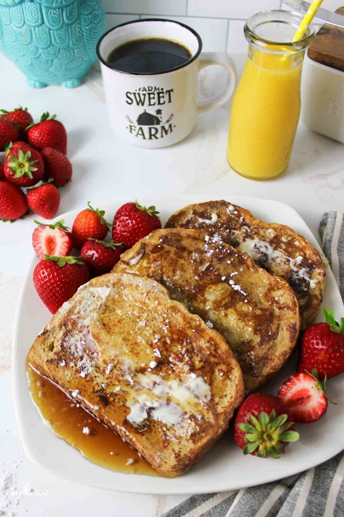 a downward angled view of a plate filled with syrup topped french toast and fresh strawberries