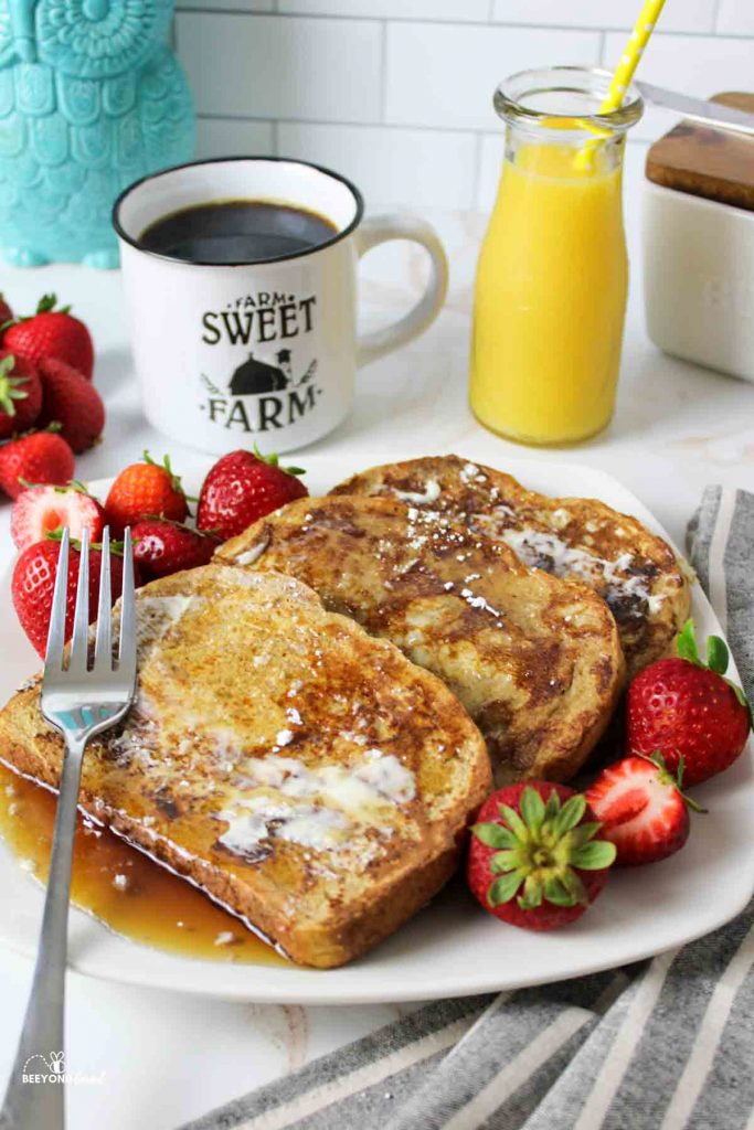 a plate full of syrup covered french toast with fresh strawberryies and a fork and some drinks in the background