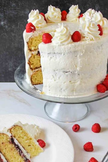 a white frosted cake with raspberries and a slice removed and placed on a plate to the side near scattered raspberries