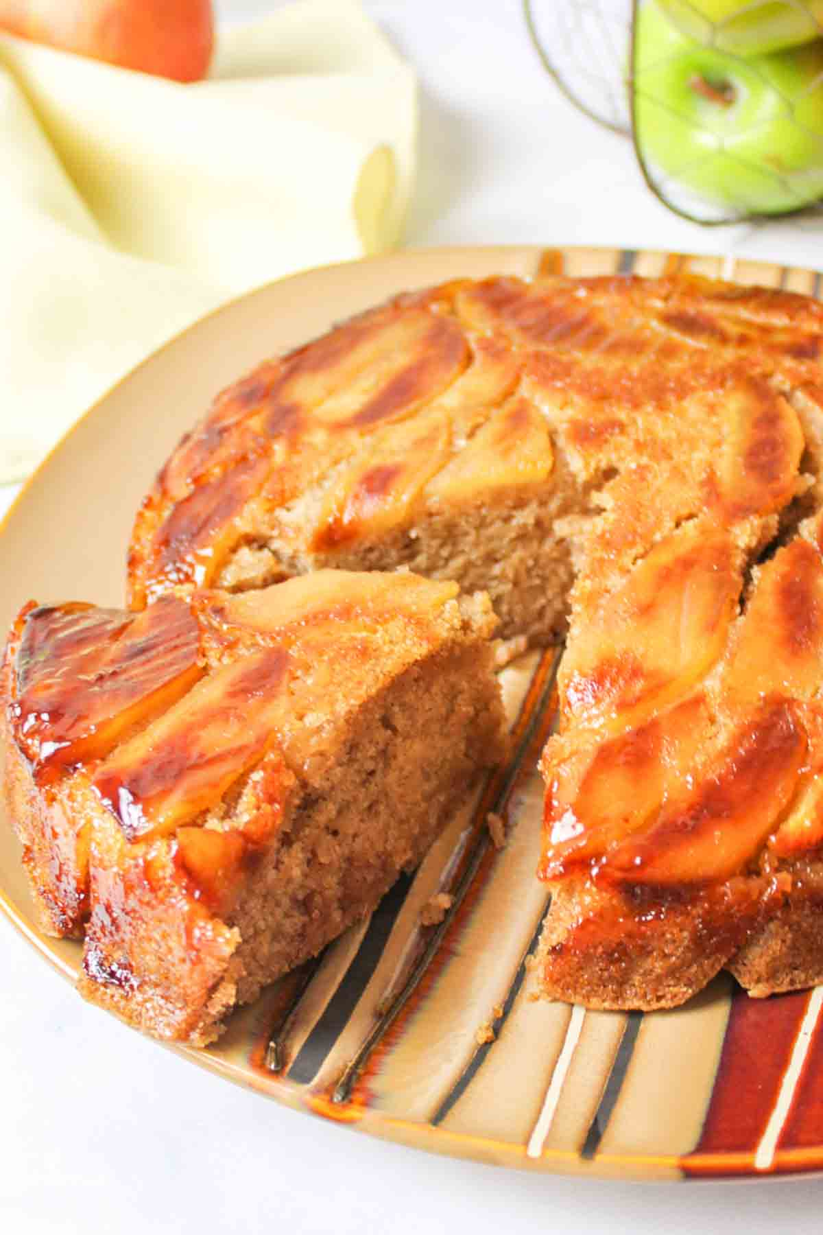 a slice being cut and pulled away from the whole apple upside down cake