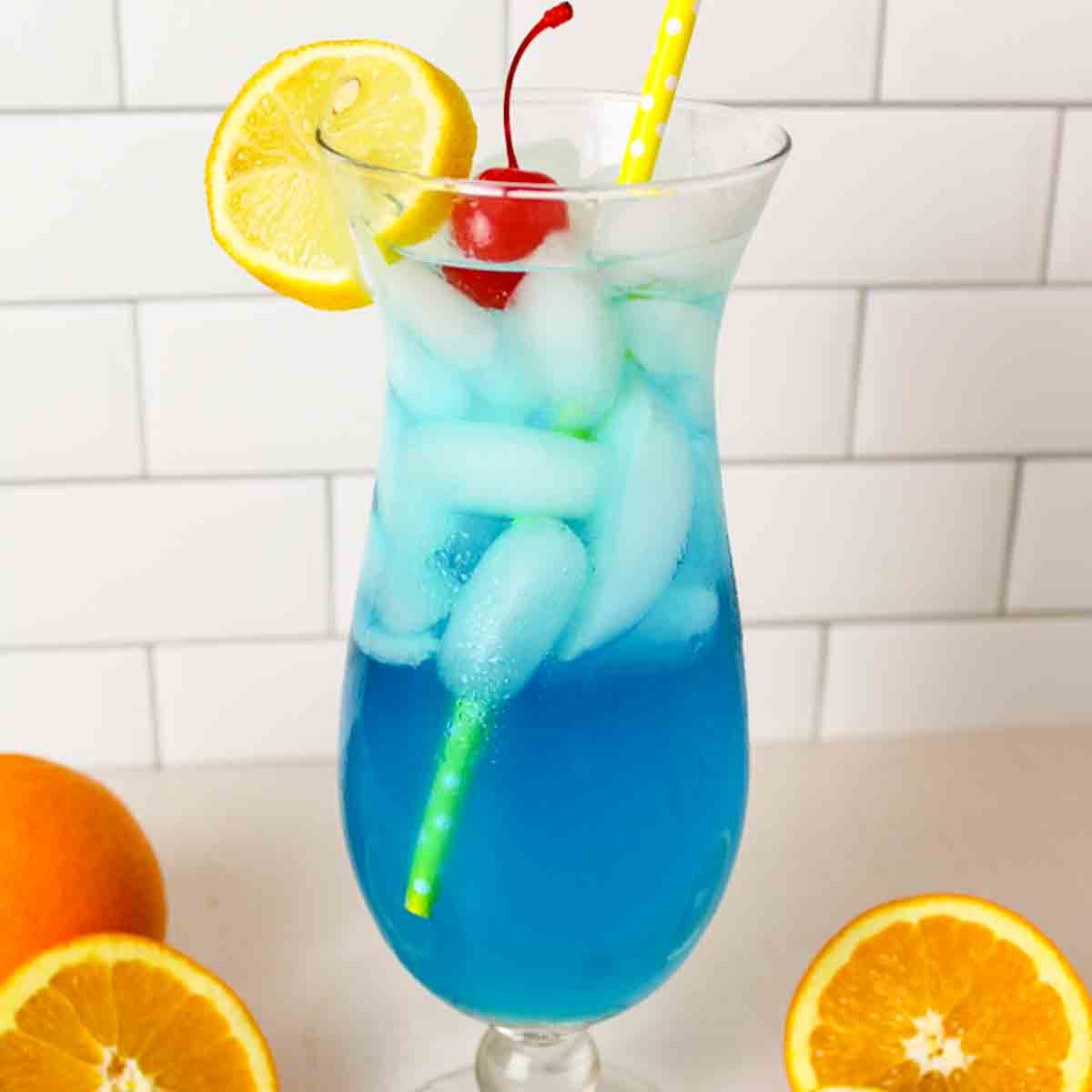 a close up of a blue lagoon mocktail in a glass and garnished with cherry and lemon slice