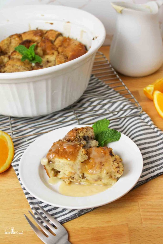 a slice of bread pudding on a white plate with more in a round casserole dish behind it