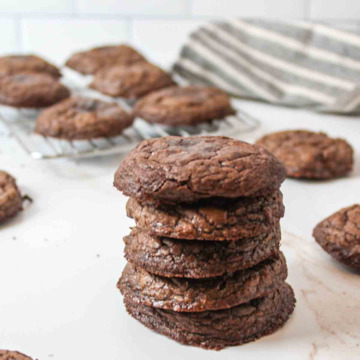 an upclose view of a stack of brownie mix cookies with more in the background