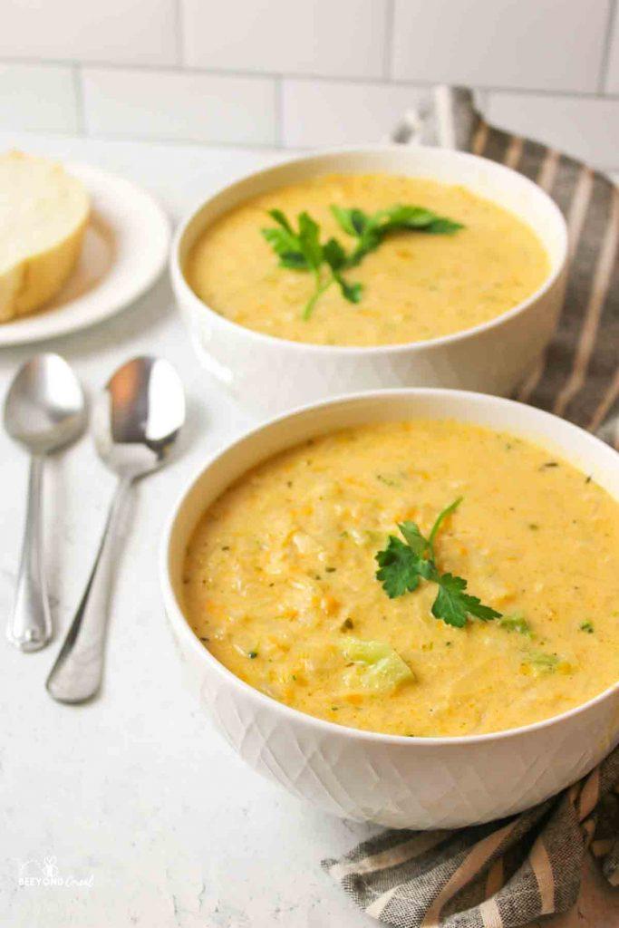 two bowls of potato soup next to two spoons