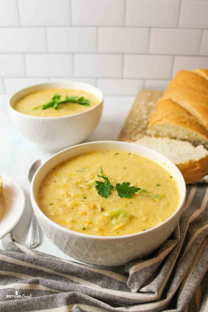 two white bowls filled with cheesy potato soup and topped withparsely next to a cutting board full fo sliced bread loaf