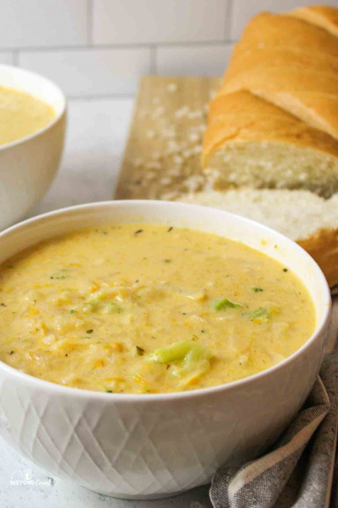 a close up of a bowl filled with cheddar potato soup with bread loaf sliced in background