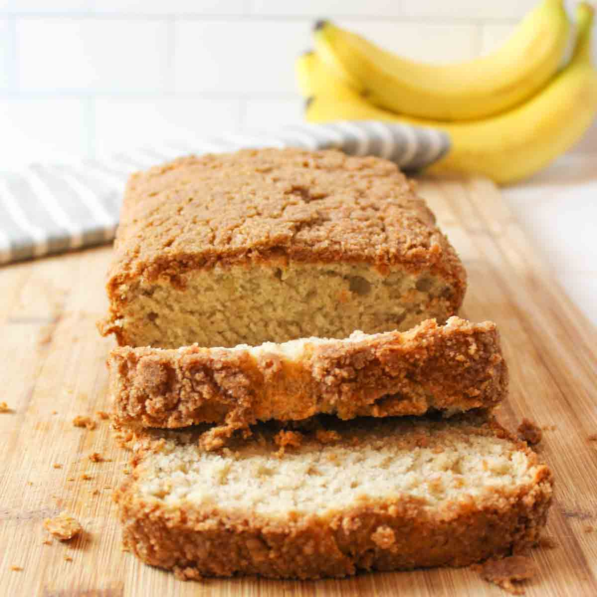 a close view of sliced banana bread on a cutting board with ripe bananas in background
