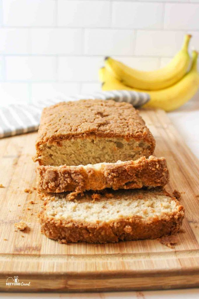 a straightforward shot of sliced banana bread with two slices folded downward on a wooden cutting board and yellow bananas in background