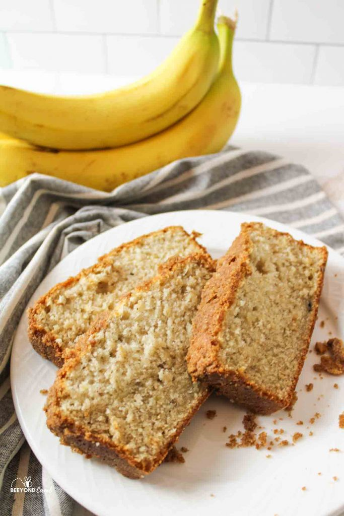 three slices of cinamon crumble banana bread on a plate next to a striped towel and fresh bananas