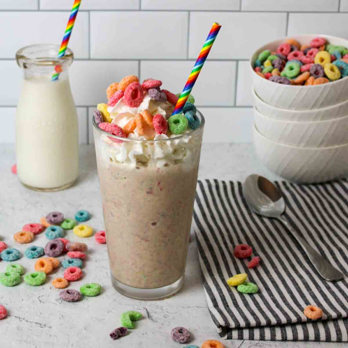 a glass full of fruit loops milkshake with scattered cereal around it and bowlf of creeal and bottle of milk in background