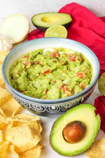 an upclose view of a blue bowl filled with guacamole without cilantro and scattered ingredients and chips around it