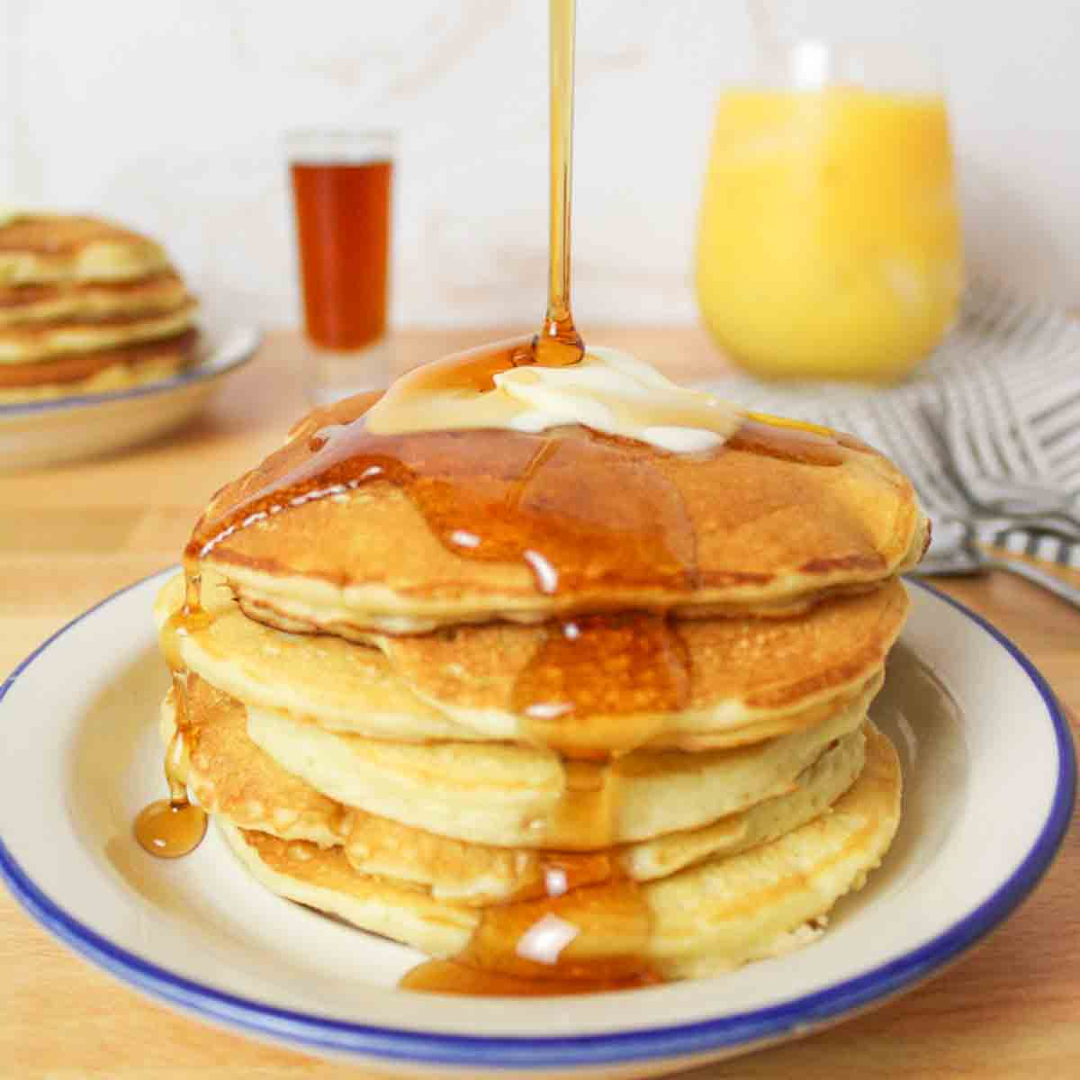 syrup drizzling over the top of butter topped pancakes