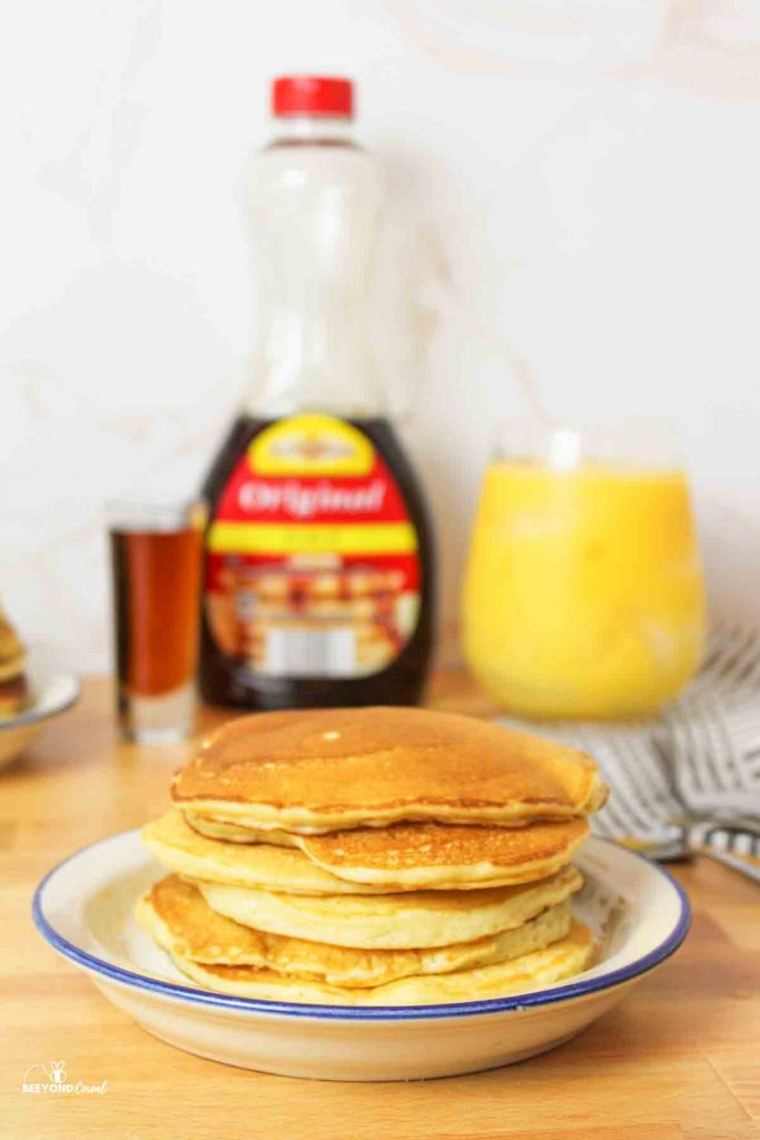 a stack of golden pancakes on a blue rimmed plate with syrup and orange juice in background