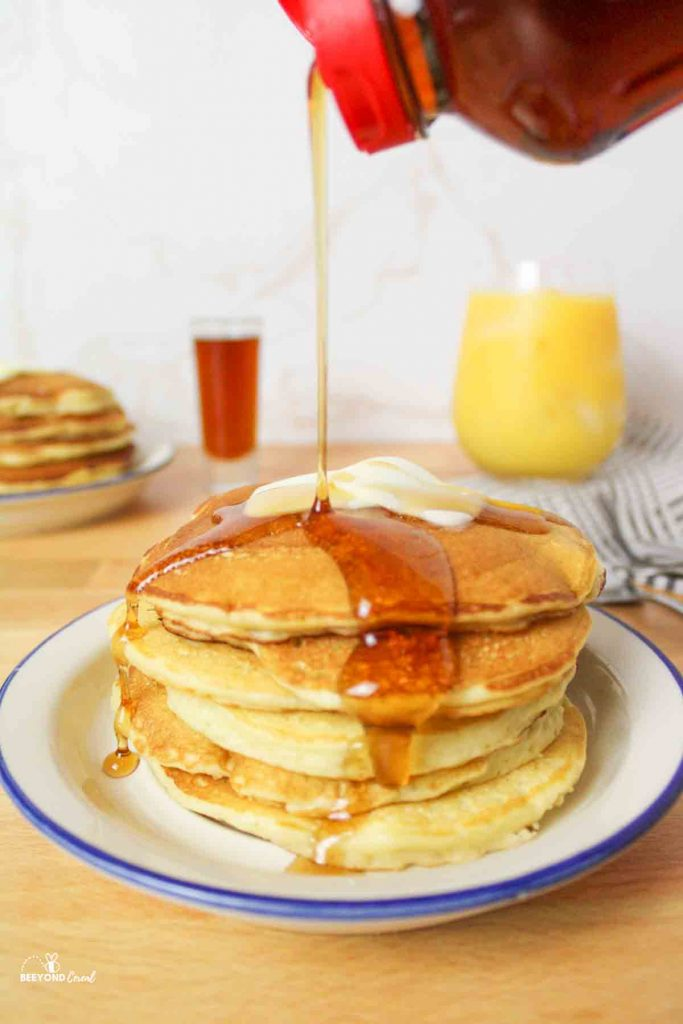 a syrup bottle squirting syrup over the top of a stack of pancakes on a plate