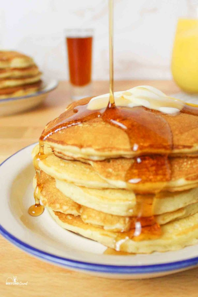 a drizzle of syrup landing on a stack of pancakes with butter on top