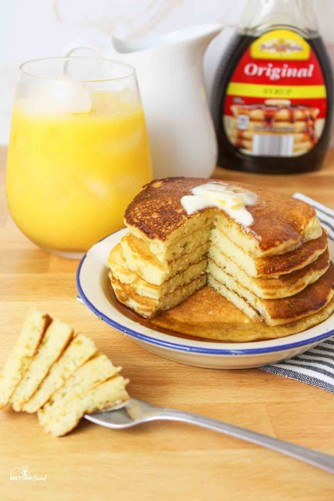 a stack of pancakes on a plate with a fork full of a large bitesworth