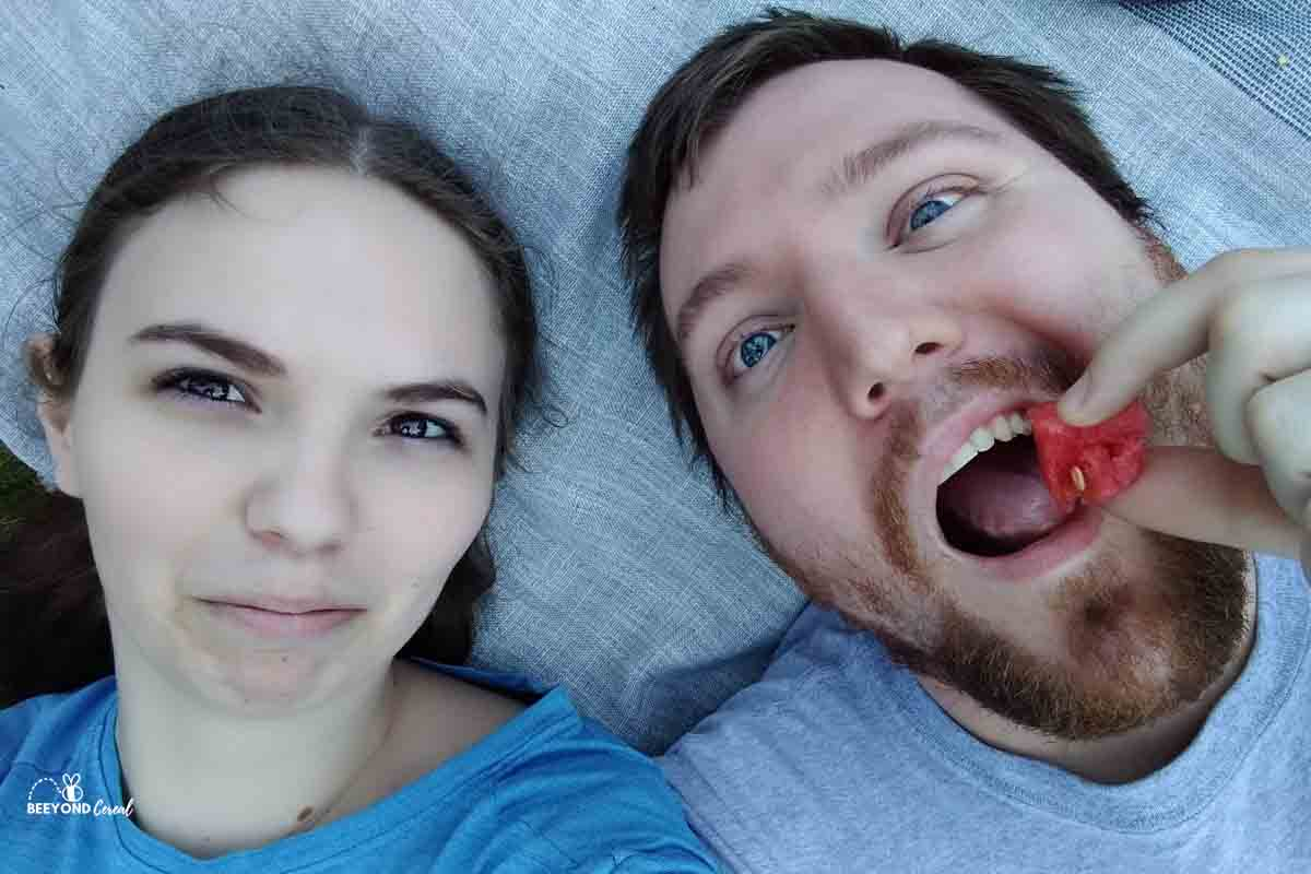 nicole and husband in a selfie while he eats watermelon