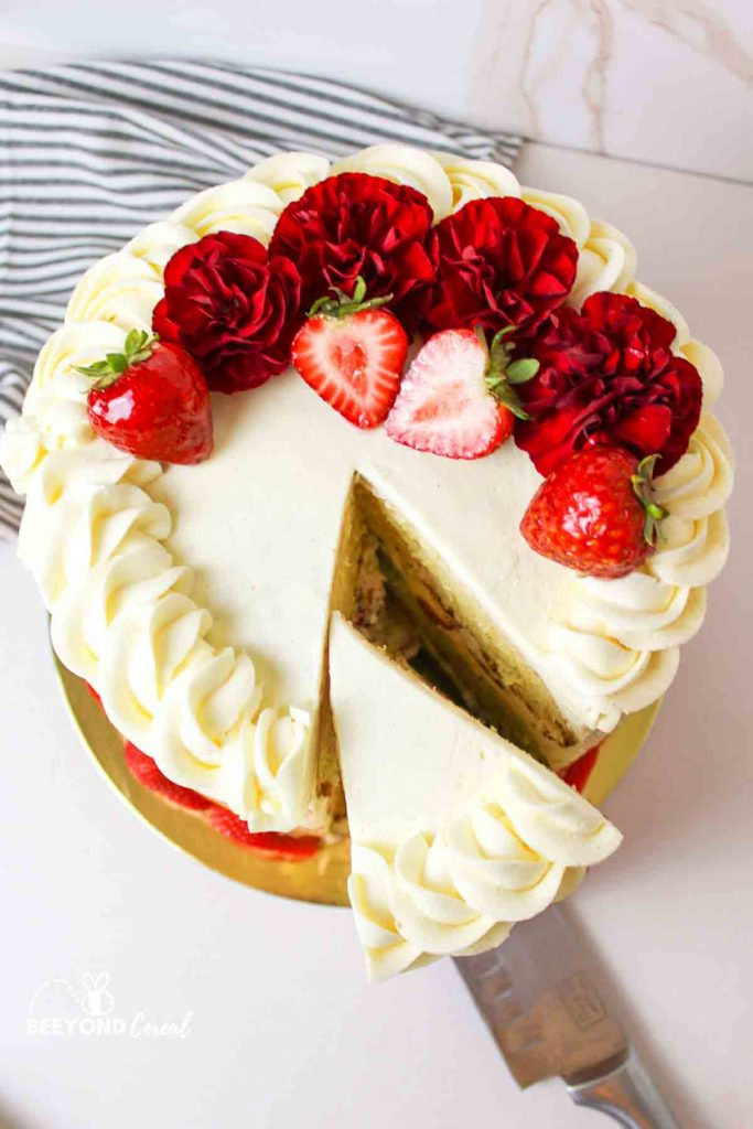 aerial view of a sliced tres leches cake with strawberries and flowers on top