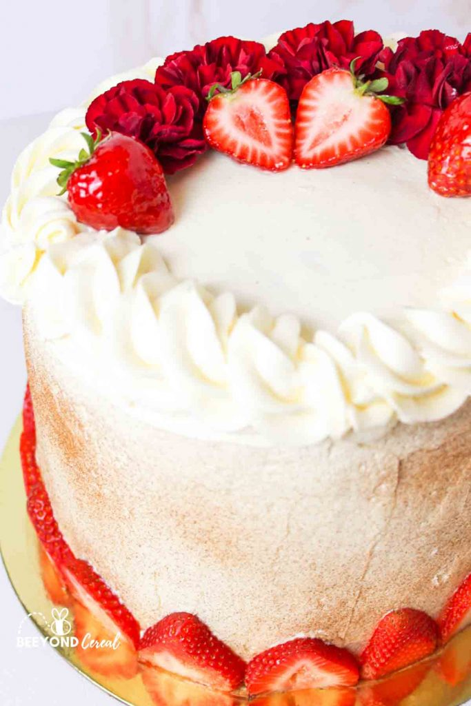 tall tres leches laered cake with strawberries and red flowers for garnish