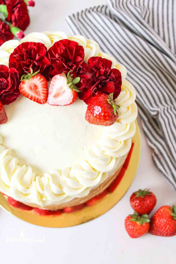 aerial view of a flower and strawberry topped tres leches cake next to striped towel
