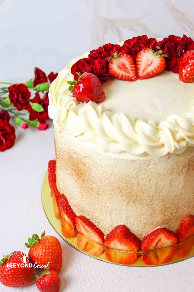 a strawberry and red flower garnishes tres leches cake with more berries and flowers to the side