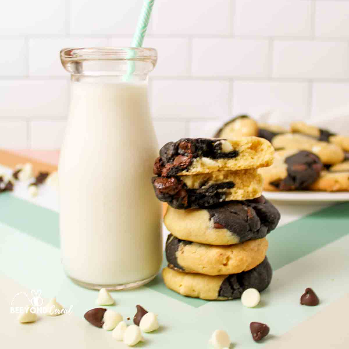 a glass of milk next to a stack of marbled chocolate chip cookies and scattered chocolate chips